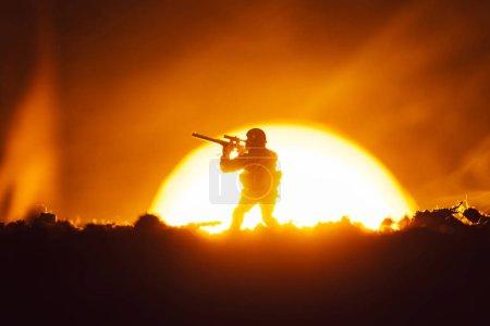 Photo pour Soldat jouet avec fumée et coucher du soleil à l'arrière-plan, scène de combat - image libre de droit