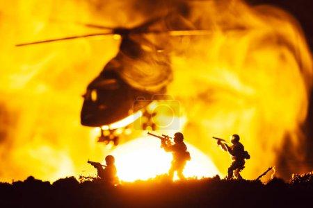 Photo pour Scène de combat avec des guerriers jouet et un hélicoptère en fumée avec coucher du soleil à l'arrière-plan - image libre de droit