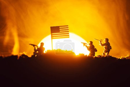 Photo pour Scène de bataille avec des guerriers jouets près du drapeau américain en fumée avec coucher de soleil en arrière-plan - image libre de droit
