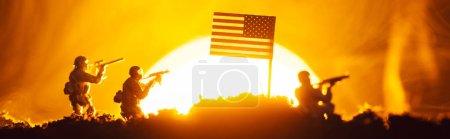 Photo pour Scène de combat avec des guerriers jouet près d'un drapeau américain en fumée avec coucher du soleil en arrière-plan, photo panoramique - image libre de droit