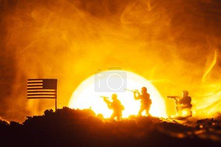 Photo pour Scène de bataille de soldats jouets, drapeau américain et feu avec coucher de soleil en arrière-plan - image libre de droit