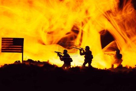 Photo pour Scène de combat avec des guerriers jouet près d'un drapeau américain avec feu en arrière-plan - image libre de droit