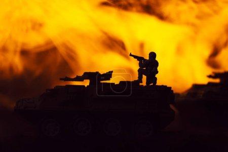 Photo pour Scène de combat avec silhouettes de guerrier jouet et chars avec feu en arrière-plan - image libre de droit