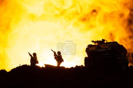 Photo pour Scène de combat avec silhouettes de char jouet et soldats avec feu en arrière-plan - image libre de droit