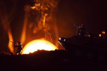 Photo pour Scène de combat avec guerriers jouet et char en fumée avec coucher du soleil à l'arrière-plan - image libre de droit