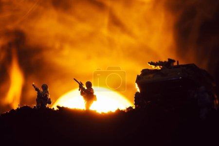 Photo pour Silhouettes de guerriers jouet et de chars sur le champ de bataille avec coucher du soleil et feu à l'arrière-plan - image libre de droit