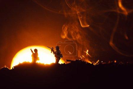 Photo pour Scène de combat avec des soldats jouets sur le champ de bataille avec fumée et coucher du soleil à l'arrière-plan - image libre de droit