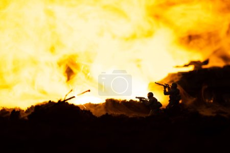 Photo pour Scène de combat avec soldats jouet et char sur le champ de bataille avec feu à l'arrière-plan - image libre de droit
