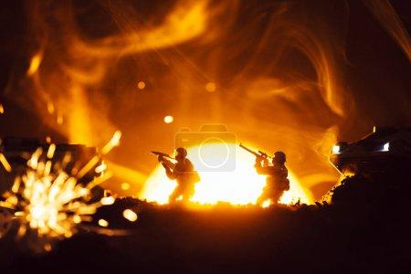 Foto de Enfoque selectivo de guerreros de juguete con tanques cerca de explosión y humo con puesta de sol en el fondo - Imagen libre de derechos