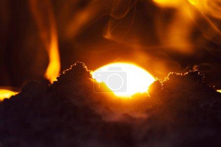 Photo pour Mise au point sélective des tas de terre avec fumée et coucher de soleil sur fond noir - image libre de droit