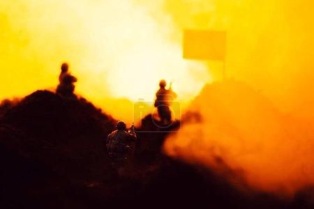 Photo pour Concentration sélective des guerriers jouets sur le champ de bataille avec fumée, drapeau et feu en arrière-plan - image libre de droit