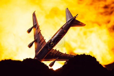 Photo for Battle scene with crash of toy plane with fire at background - Royalty Free Image