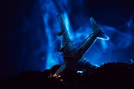 Photo pour Scène de combat avec écrasement d'un avion jouet avec de la fumée bleue sur fond noir - image libre de droit