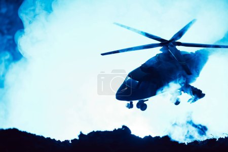 Photo for Battle scene with toy helicopter above battleground with smoke on blue background - Royalty Free Image
