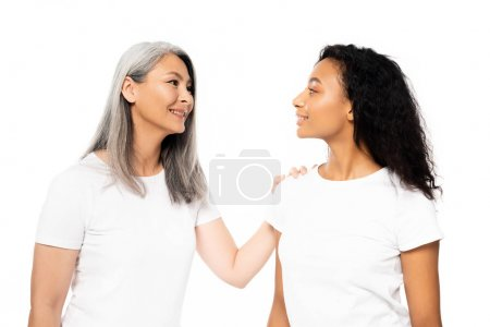 Photo pour Attractive african american and asian women looking at each other isolated on white - image libre de droit