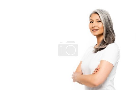 Photo for Happy asian woman looking at camera and standing with crossed arms isolated on white - Royalty Free Image