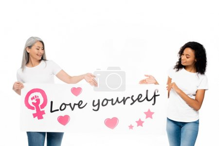 Photo pour Happy african american and asian women pointing with hands at placard with love yourself lettering isolated on white - image libre de droit