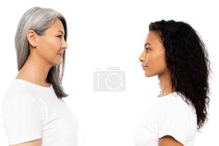 Photo for Side view of happy african american and asian women looking at each other isolated on white - Royalty Free Image
