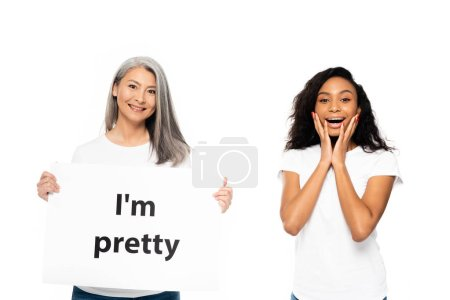 Photo for Happy african american and asian women near i`m pretty placard isolated on white - Royalty Free Image