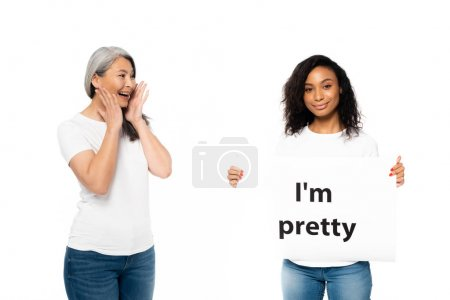 Photo pour Smiling african american and asian women near I'm pretty placard isolated on white - image libre de droit