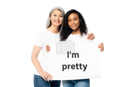 Photo for Smiling african american and asian women holding i`m pretty placard isolated on white - Royalty Free Image