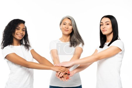 Photo for Cheerful multicultural women putting hands together isolated on white - Royalty Free Image