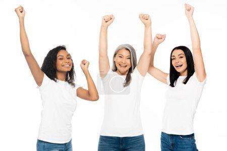 emocionadas mujeres multiculturales con las manos encima de la cabeza celebrando aisladas en blanco