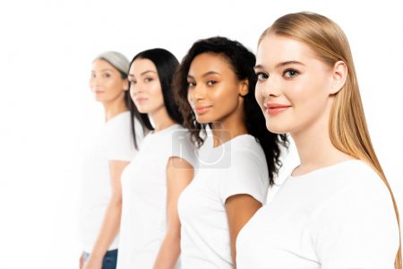 Photo pour Foyer sélectif de quatre femmes multiculturelles en t-shirts blancs regardant la caméra isolée sur blanc - image libre de droit