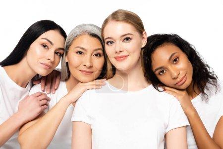 Photo pour Des femmes multiculturelles gaies en t-shirts blancs regardant une caméra isolée sur - image libre de droit