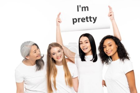 Photo pour Happy multicultural women near placard with I'm pretty lettering isolated on white - image libre de droit