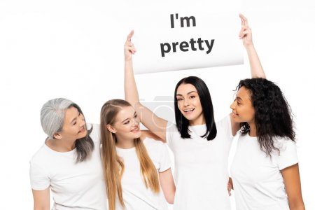 Photo pour Four multicultural women near placard with I'm pretty lettering isolated on white - image libre de droit