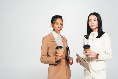 Photo pour Femmes d'affaires multiculturelles tenant des tasses jetables isolées sur blanc - image libre de droit