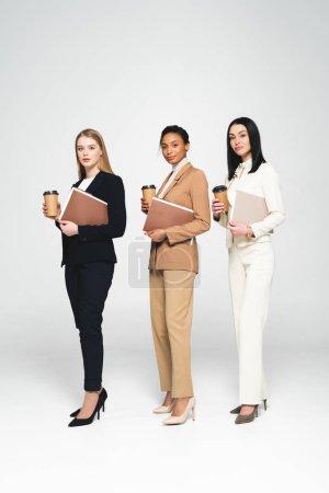 Photo pour Femmes d'affaires multiculturelles tenant des tasses et des dossiers jetables sur blanc - image libre de droit