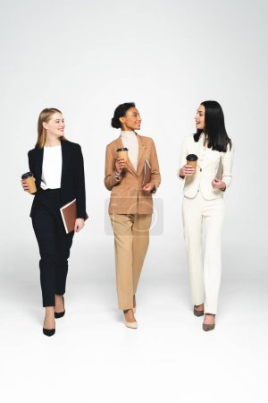 Photo for Multicultural businesswomen holding paper cups and folders on white - Royalty Free Image