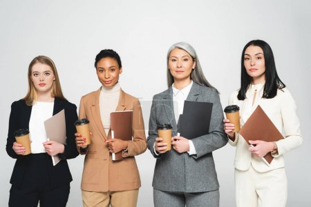 Photo for Four multicultural businesswomen holding folders and paper cups isolated on white - Royalty Free Image