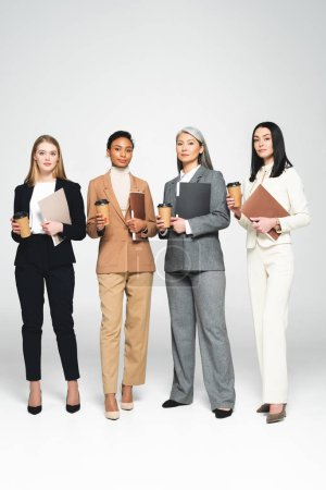 Photo for Four multicultural businesswomen holding folders and paper cups while standing on white - Royalty Free Image