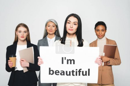 Photo pour Femmes d'affaires multiculturelles tenant des chemises et des gobelets jetables près d'une plaque avec I'm belle lettrage isolé sur blanc - image libre de droit