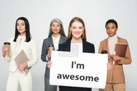 Photo for Multicultural businesswomen holding folders and disposable cups near placard with i`m awesome lettering isolated on white - Royalty Free Image