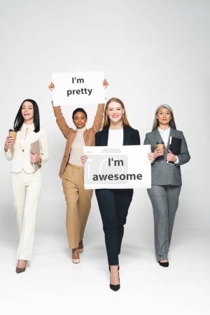 Photo for Multicultural businesswomen holding disposable cups near placards with lettering on white - Royalty Free Image