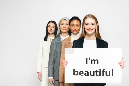 Photo pour Smiling multiculturel business women near placard with I'm beautiful lettering isolated on white - image libre de droit