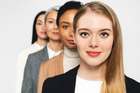 Foto de Enfoque selectivo de cuatro mujeres de negocios atractivas y multiculturales que miran la cámara aislada en blanco. - Imagen libre de derechos