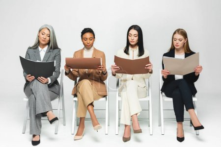 Photo pour Quatre femmes d'affaires multiculturelles en costumes assis sur des chaises et regardant des dossiers sur blanc - image libre de droit