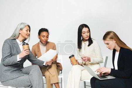 Photo pour Femmes d'affaires multiculturelles assises sur des chaises avec des gobelets de papier et un ordinateur - image libre de droit