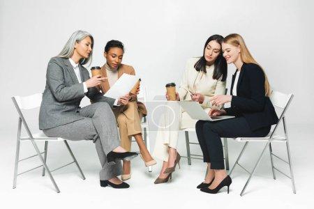 Photo pour Heureuses femmes d'affaires multiculturelles assises sur des chaises avec des tasses en papier et ordinateur portable sur blanc - image libre de droit