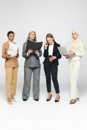 Photo pour Attractive multicultural business women with folders near woman talking on smartphone on white - image libre de droit