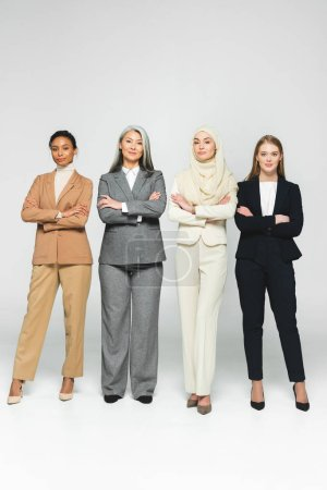 Photo pour Beautiful multicultural women standing with crossed arms on white - image libre de droit