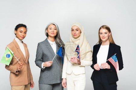 Photo pour Femmes multiculturelles avec des drapeaux de différents pays isolés sur blanc - image libre de droit