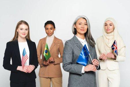 Photo pour Femmes d'affaires multiculturelles avec des drapeaux de différents pays isolés sur blanc - image libre de droit