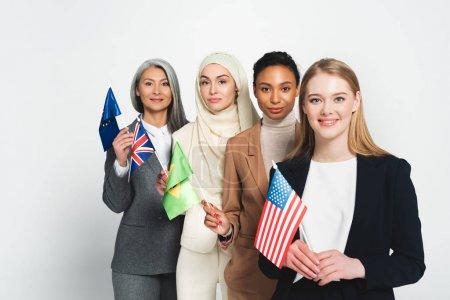 Photo pour Attrayantes femmes d'affaires multiculturelles avec des drapeaux de différents pays isolés sur blanc - image libre de droit