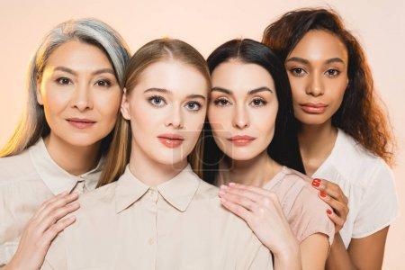 hermosas mujeres multiculturales mirando a la cámara aislada en beige